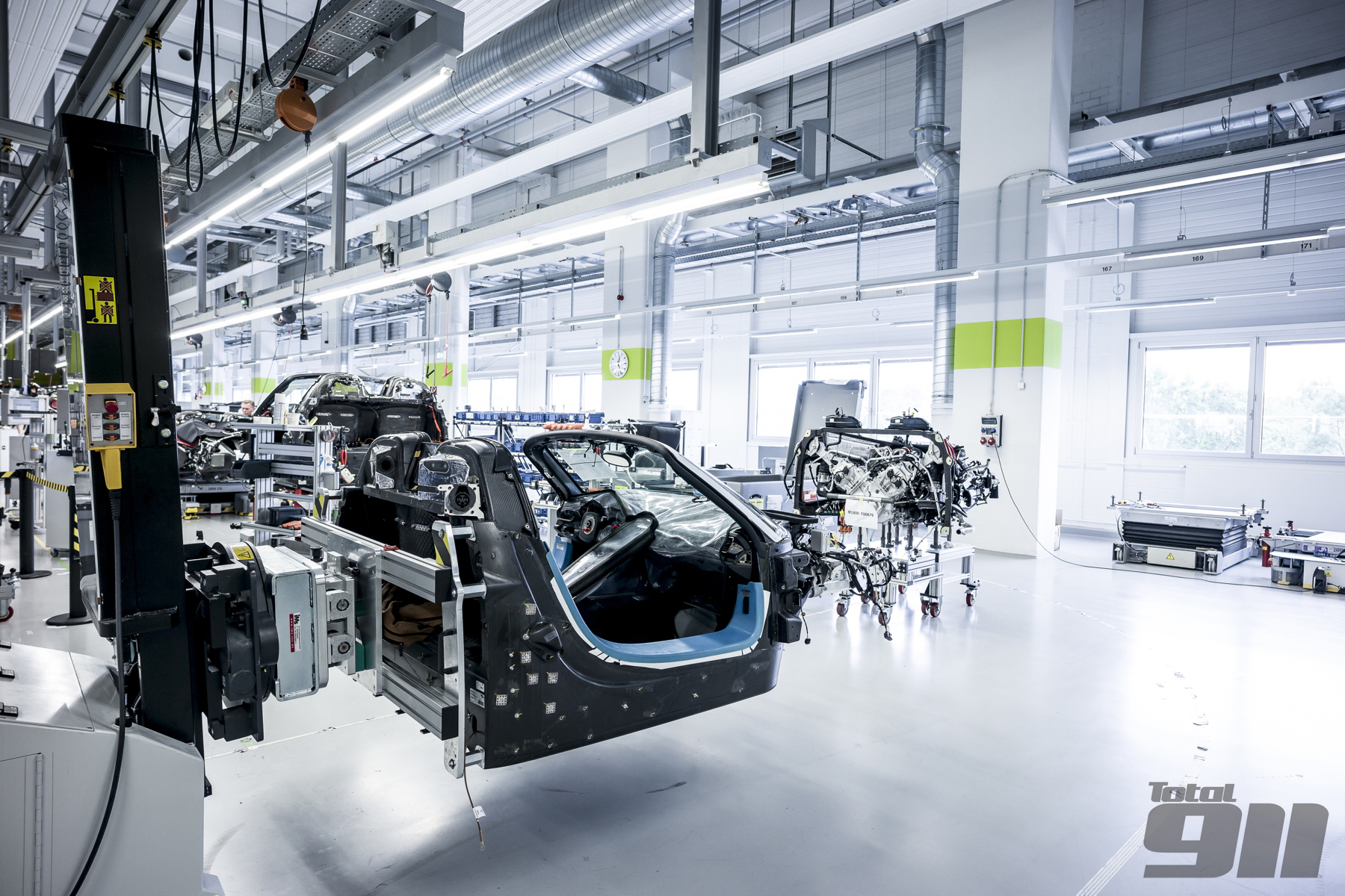 "This bare Porsche 918 Spyder awaits its engine. Porsche calls the mating of the two ""the marriage""."